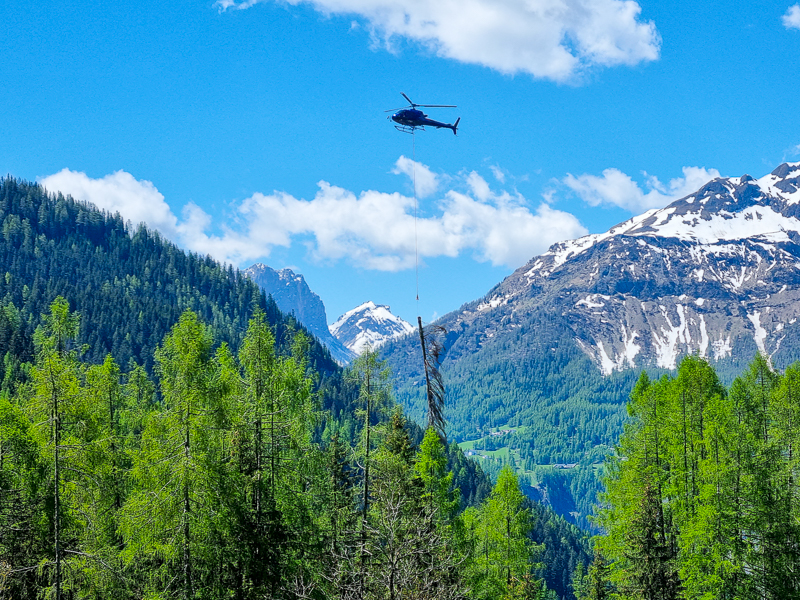 Vrtulnik zvazajuci drevo v Alpach